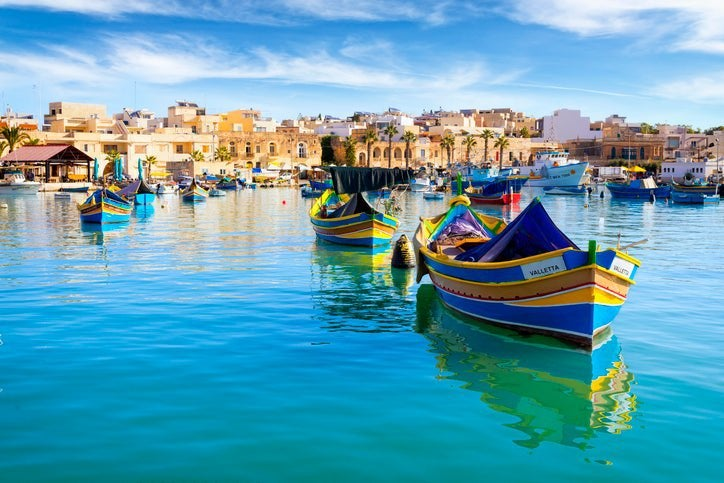 Colorful boats in a harbor with bright blue water with the Malta skyline in the background.