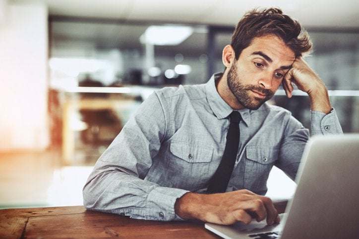 A man looking bored with his head resting on his hand while working on his computer in an office.