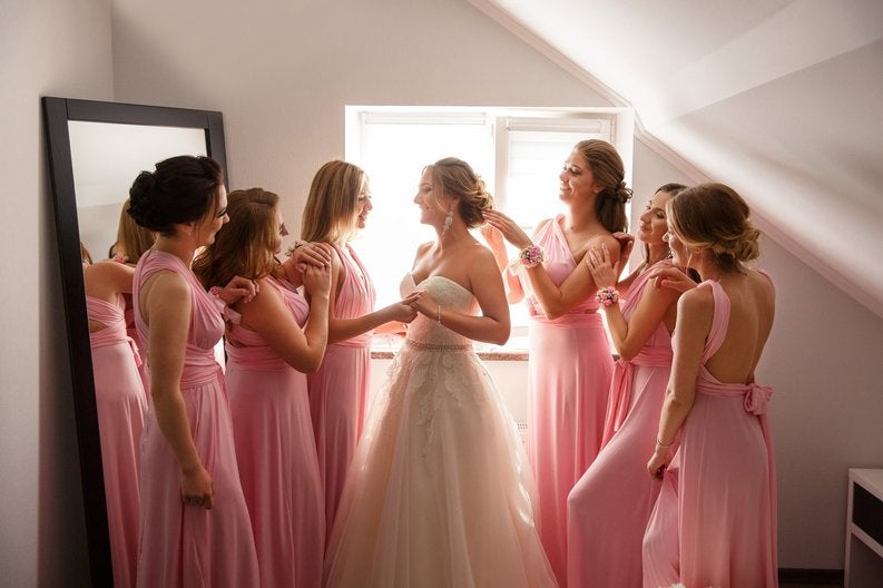 Group of women in pink dresses fawning over a bride