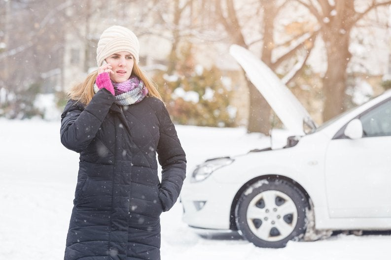Woman in coat on phone in front of car with its hood up