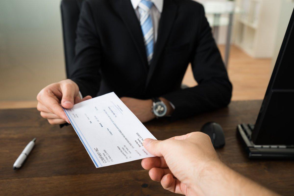 Businessman handing a paycheck to an employee.