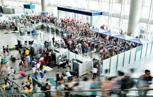 A busy airport security entrance with lots of people rushing through.