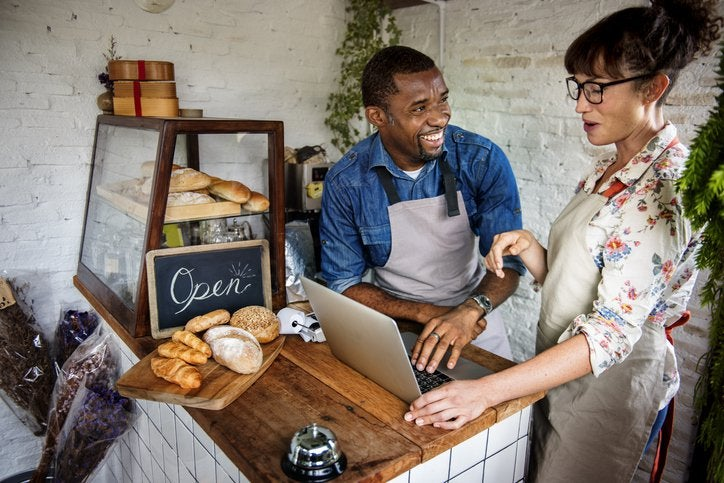 A cafe owner standing behind the counter with a laptop and joking with his employee.