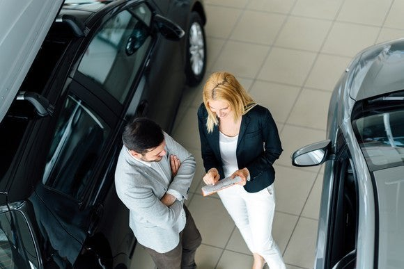 Man talking to woman at car dealership.