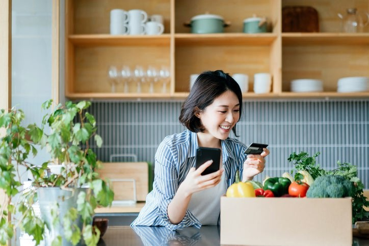 A woman in her kitchen with a phone and credit card.