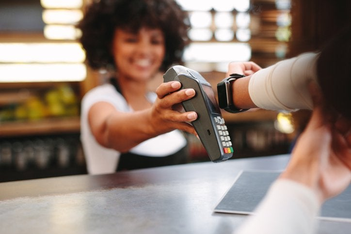 A smiling cashier holding up a payment reader for a woman paying with her smart watch.