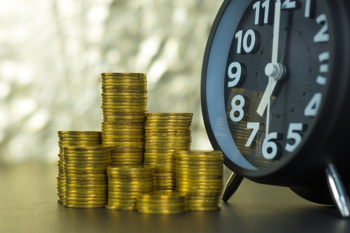 Stacks of coins next to alarm clock