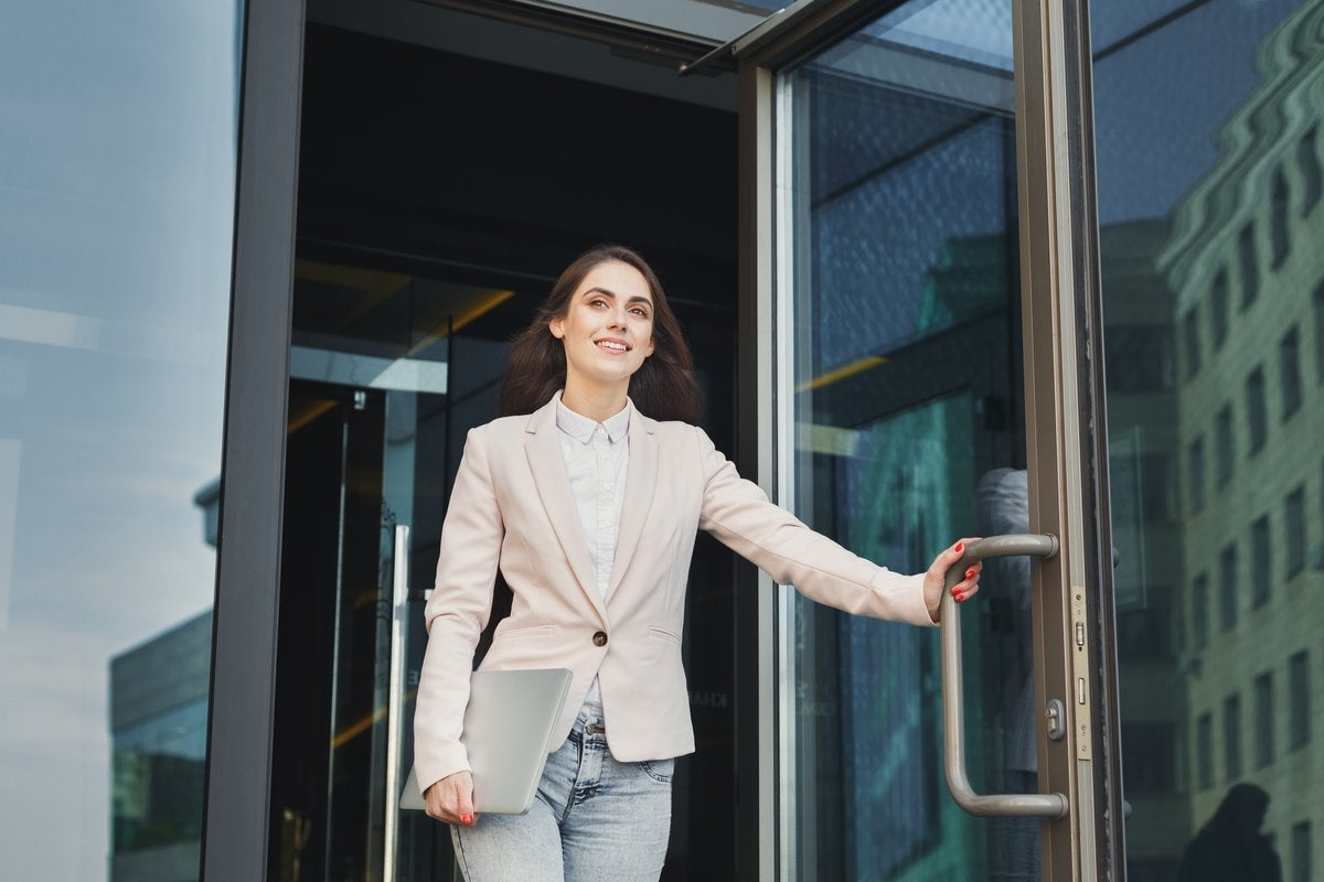smiling woman walking confidently out of building