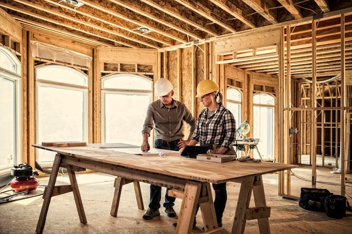 Two construction workers looking at plans on a table in a house being built.