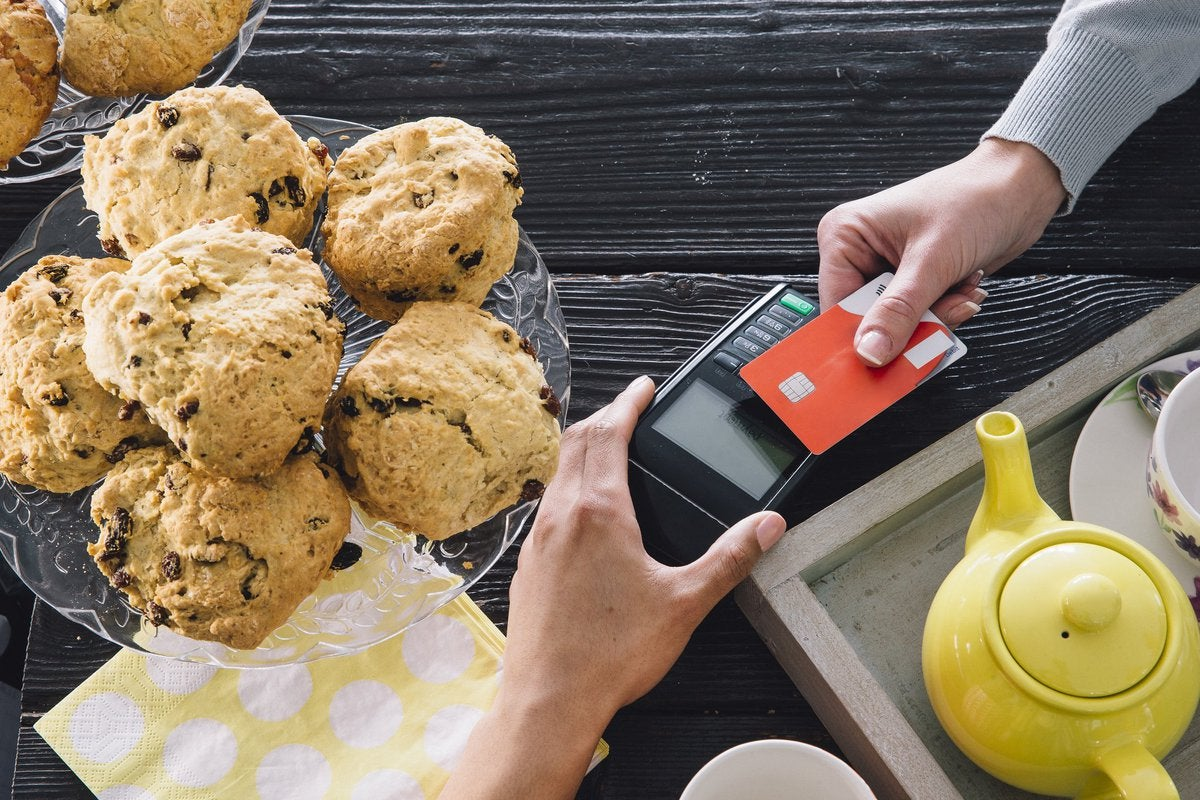 A bakery customer swiping a credit card next to a plate of muffins and a teapot.