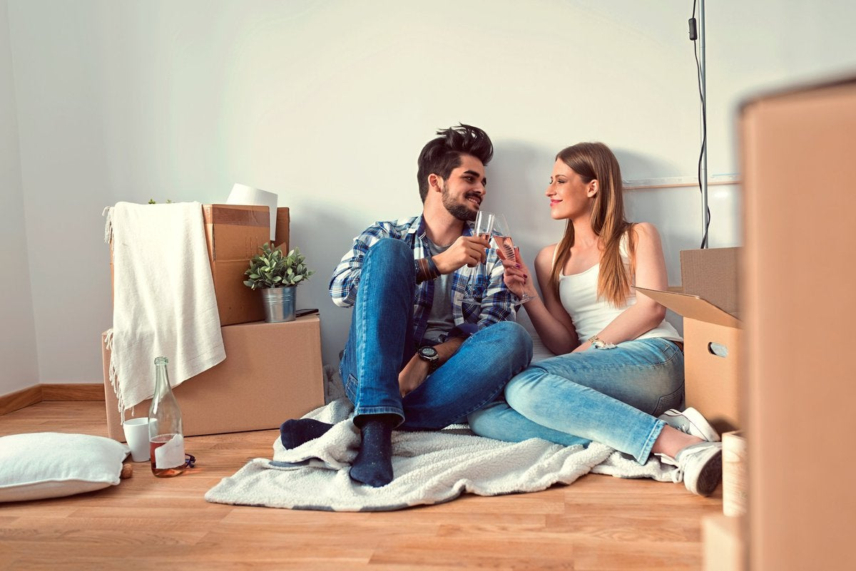 young couple sitting on floor of empty apartment surrounded by boxes and toasting with champagne