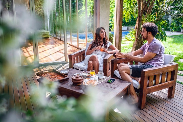 A man and woman sitting at a table on their tree-covered backyard deck and enjoying breakfast and coffee.