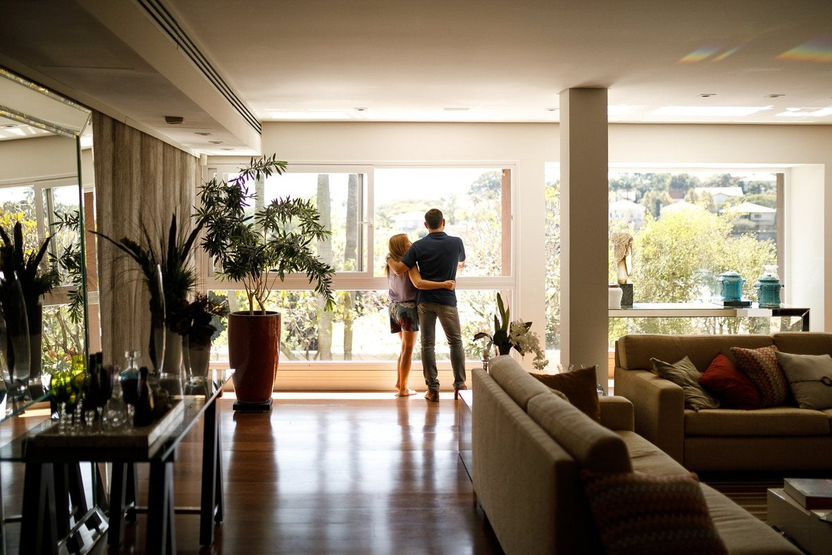 A couple with their arms around each other at the window of their home.