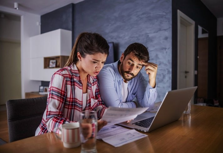 A couple looking worried about money, with a laptop and bills.