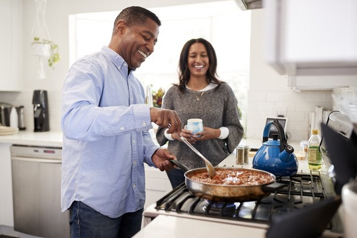 A husband cooking at the stove while his wife looks on, both of them smiling.