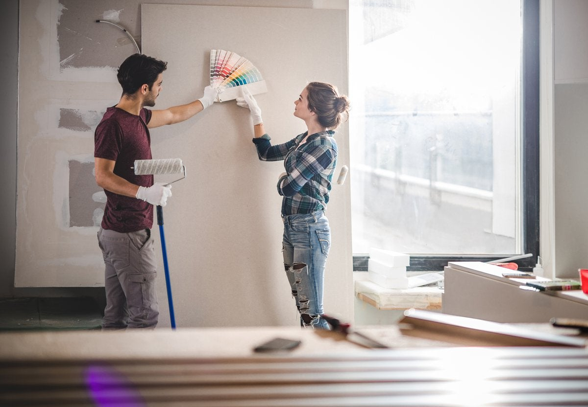 A young couple standing in their home renovation and picking out paint colors.