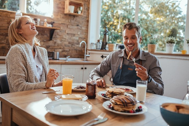 A smiling man and woman eating pancakes at their sunny kitchen table.