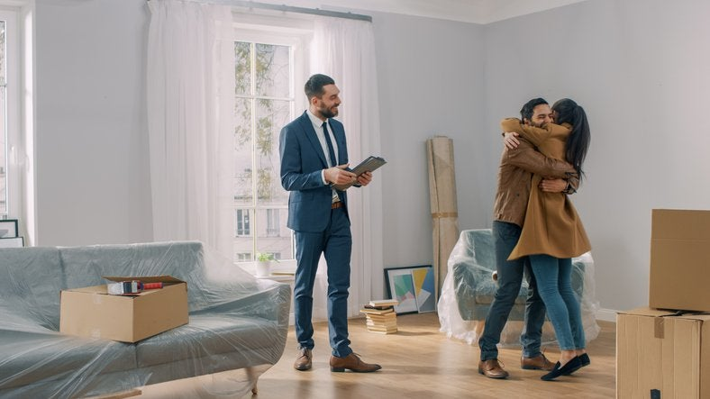 A man and woman hugging in the living room of their new house surrounded by moving boxes standing next to their realtor.