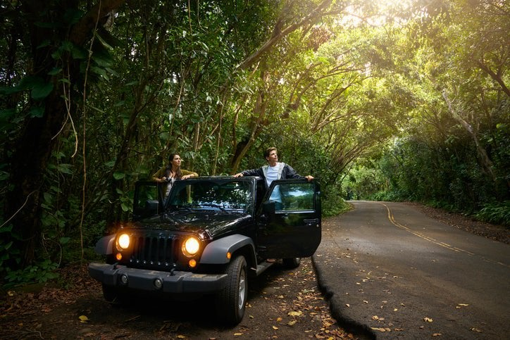 A man and woman standing in the open doors of their car parked on the side of a forest road.