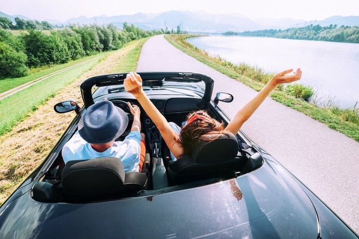 A man and woman driving down a scenic road next to a lake with the convertible top down.