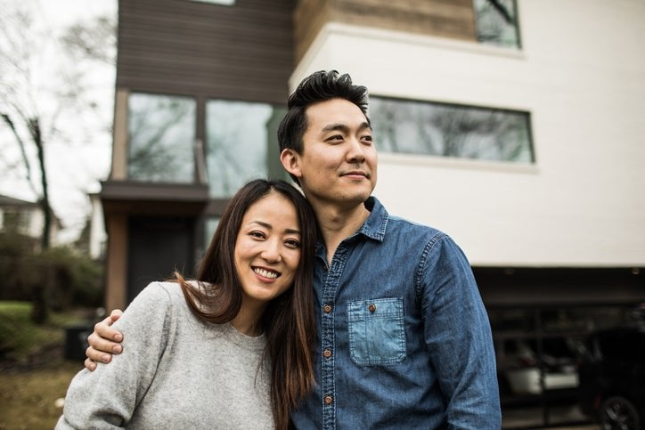 A young man and woman smiling while standing in front of their house.