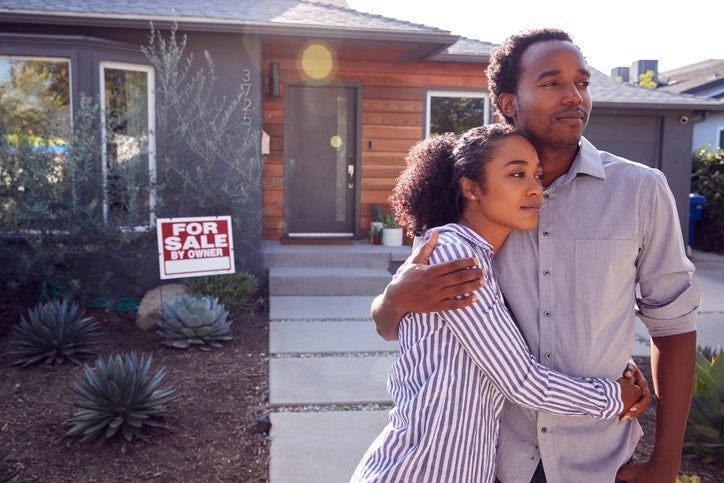 A man and woman standing with their arms around each other in front of their house with a For Sale sign behind them.