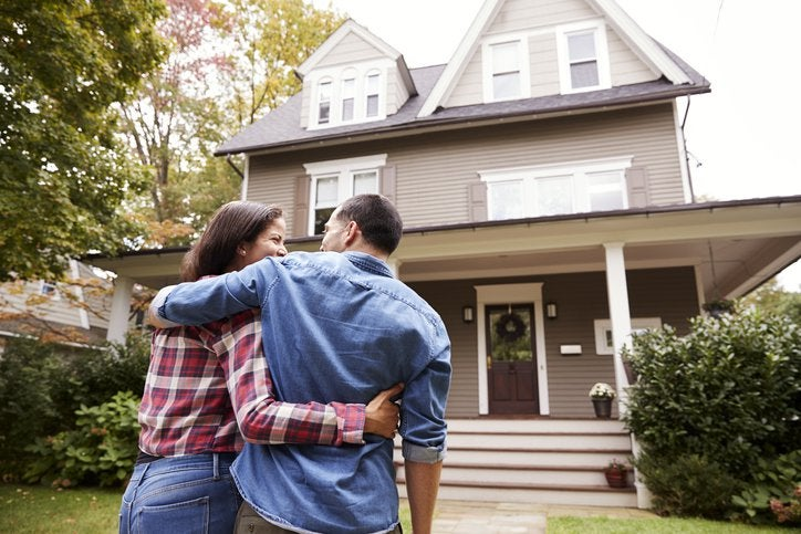 A couple with their arms around each other standing in front of their new house.