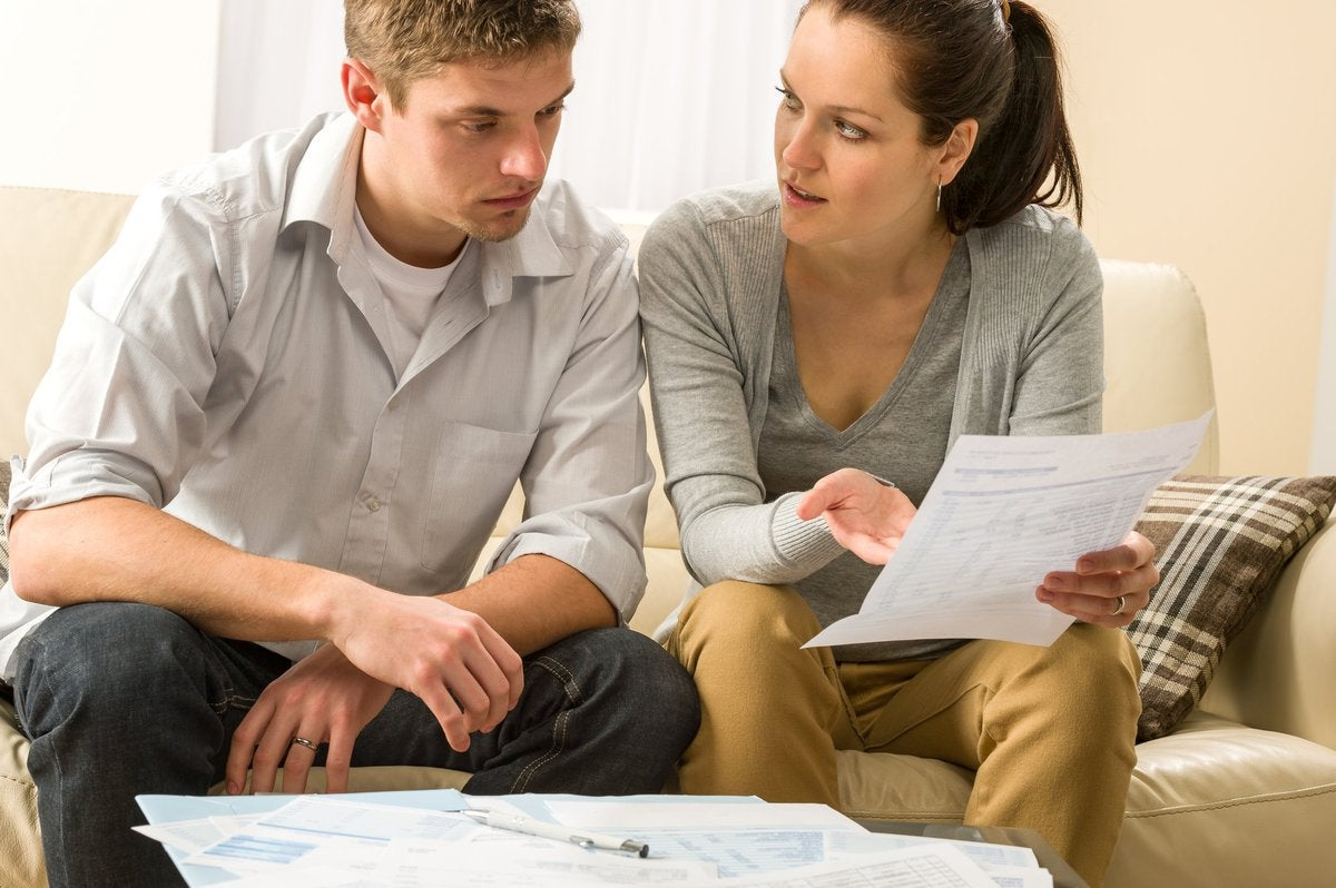 Young couple looking at bills in dismay.