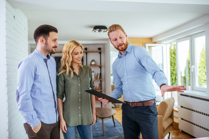 A couple looks at a house with a real estate agent.