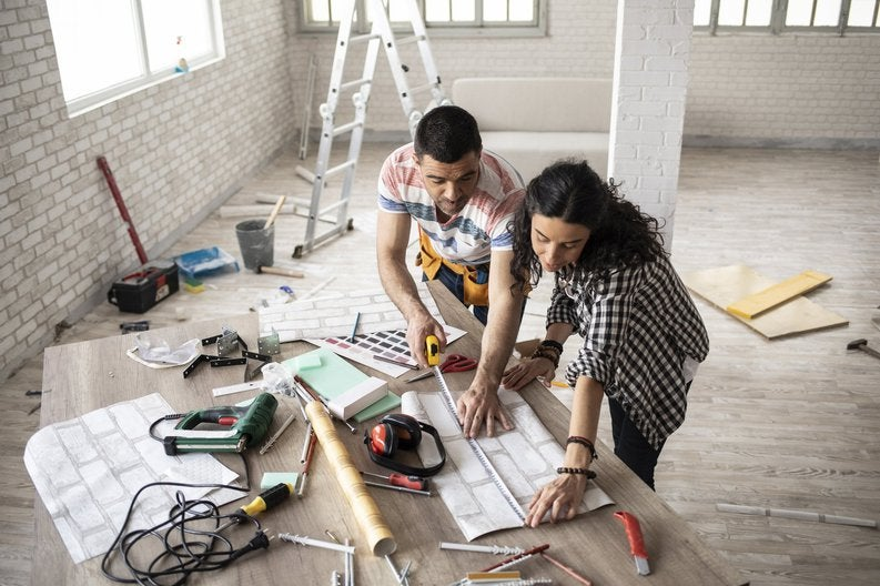 A couple in an empty loft apartment planning out home improvements.