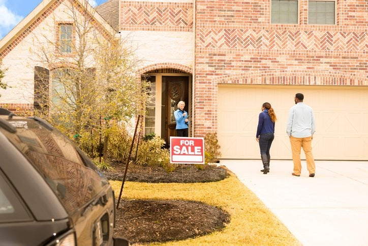A man and woman meeting their realtor at the front door of a house with a For Sale sign out front.