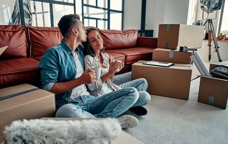 A man and woman smiling while sitting on the floor between moving boxes in the living room of their new home.