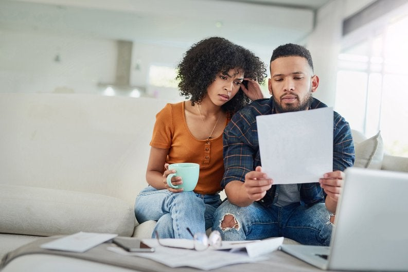 A young couple sitting on their couch and looking over their bills.