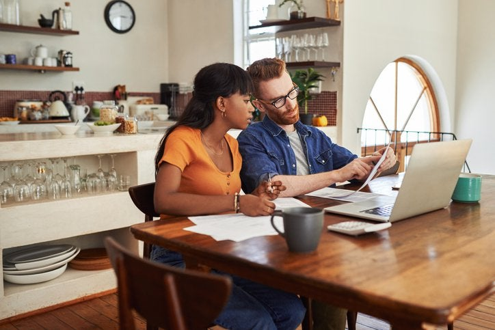 A couple reviewing bills together on a laptop while sitting in their kitchen.