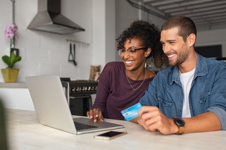 A man and woman shopping online with a credit card