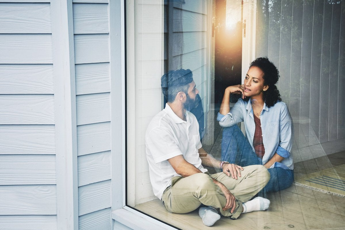 A young couple having a conversation while sitting on the floor in front of a sunny window.