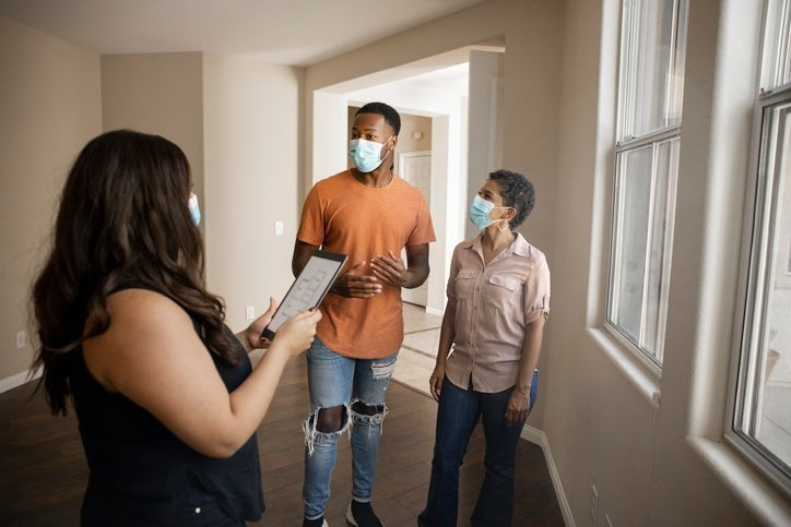 A man and woman wearing medical masks while touring an empty home with their realtor.