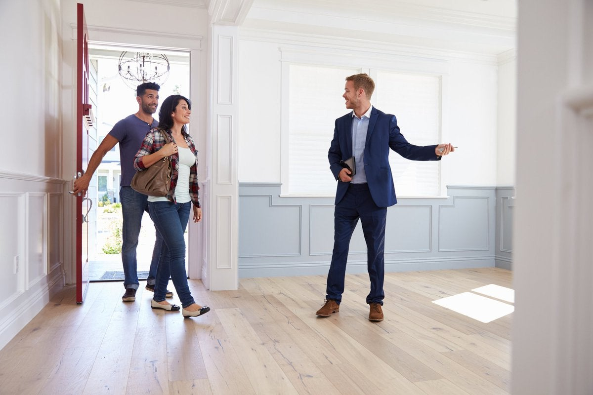 A couple touring an empty house with their realtor.
