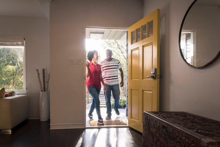 A smiling man and woman walking in the front door of their new home.