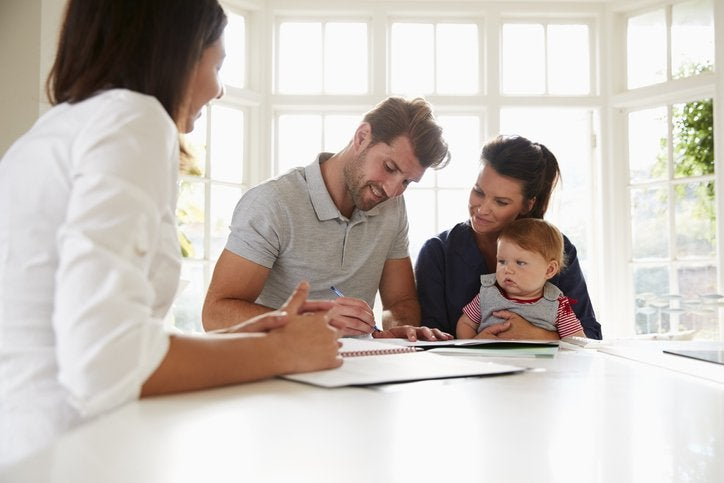 A man sitting next to his wife and baby at a sunny kitchen counter and signing documents from a female mortgage lender.