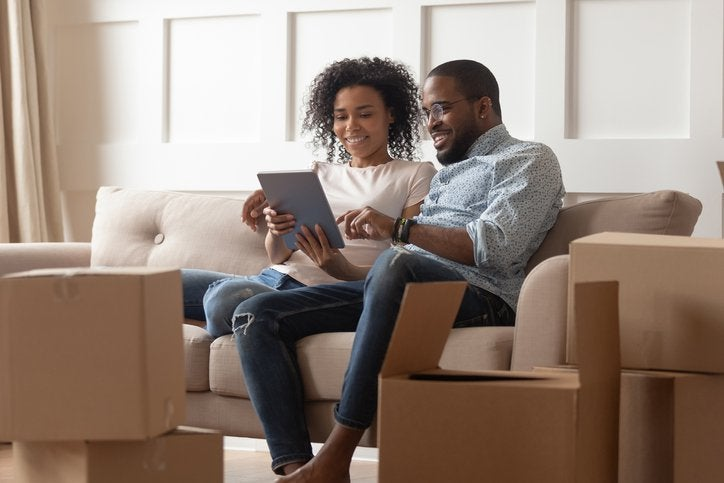 A couple looks at a pad while sitting on a couch near moving boxes