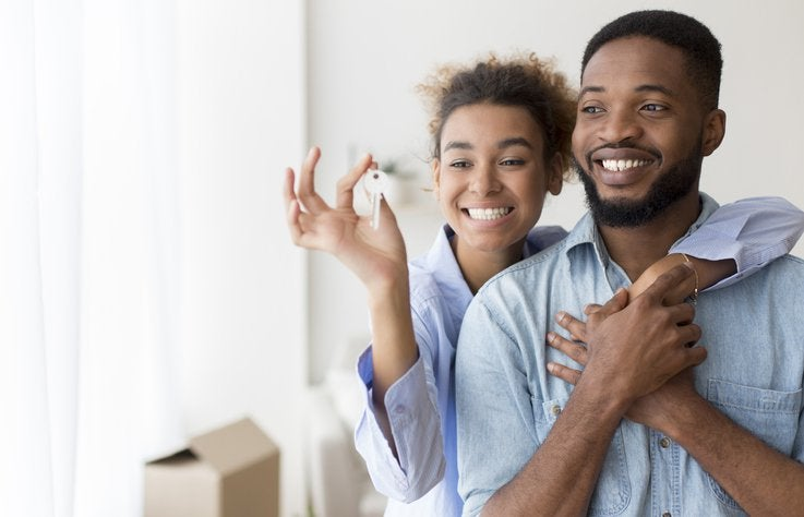 A couple holding up new house keys.