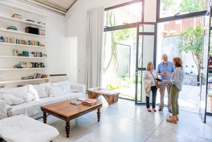 A man and woman touring the bright living room of a home with their realtor.