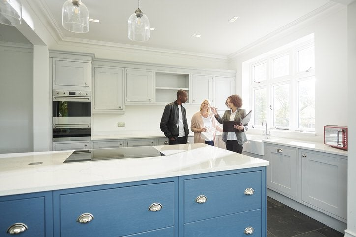 A couple touring the kitchen of a new home with their realtor.