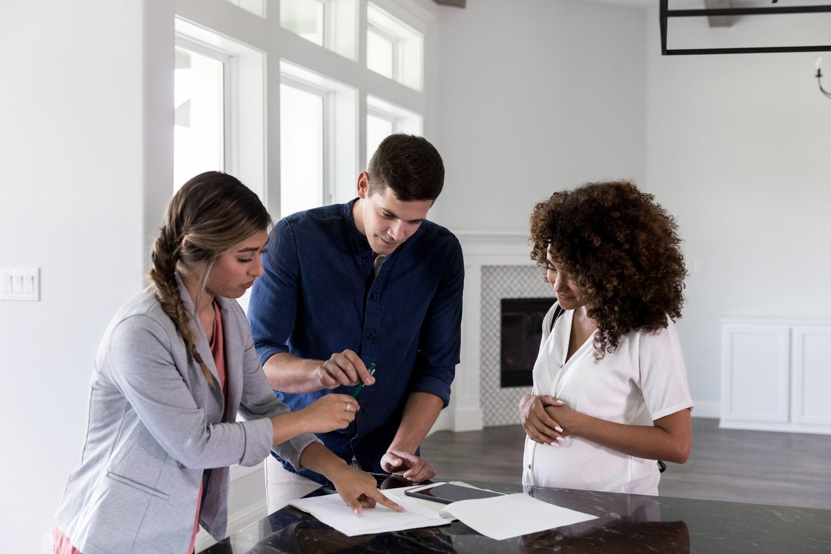 A couple standing in a new home with their realtor and signing papers.