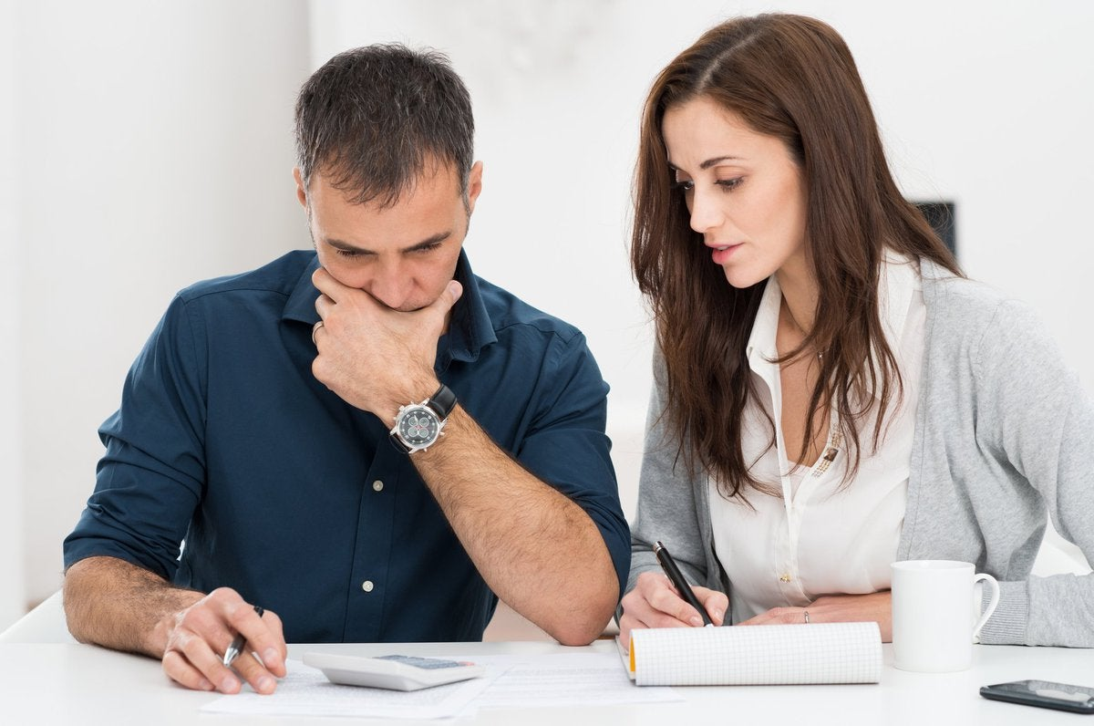 Man holding pen and looking in calculator next to woman writing in notebook