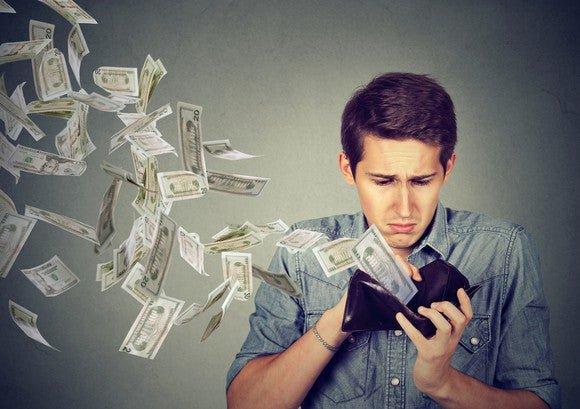 Sad man looking at his wallet, while dollar bills fly away.