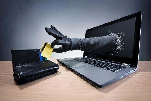 a hand in a black glove reaching out through a laptop screen to take a credit card out of a wallet