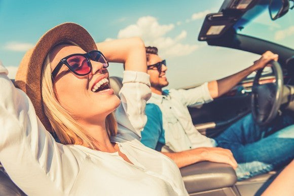 A man and a woman riding in a convertible