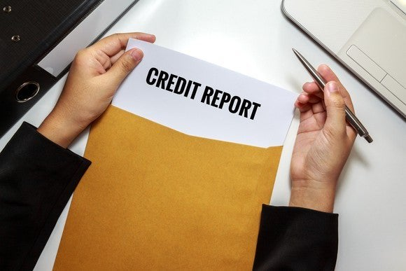 "Hands holding a manila envelope labeled ""credit report."""
